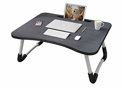 A dark grey foldable bed table with a laptop, wireless keyboard, and mouse on it. Also on the table are a cup of coffee and tablet in the tablet holder slot