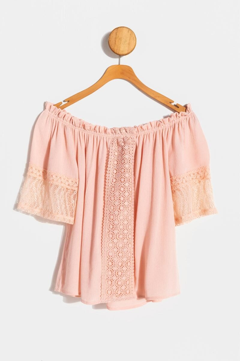 The peachy pink blouse, which has crochet details down the center and on the sleeves