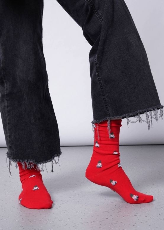 model wears red socks with tiny gnome pattern