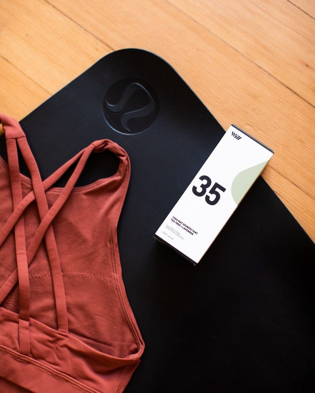 The mat spray lies on a yoga mat next to a discarded sports bra