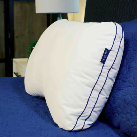 the pillow propped against headboard with indentation visible for neck and shoulders