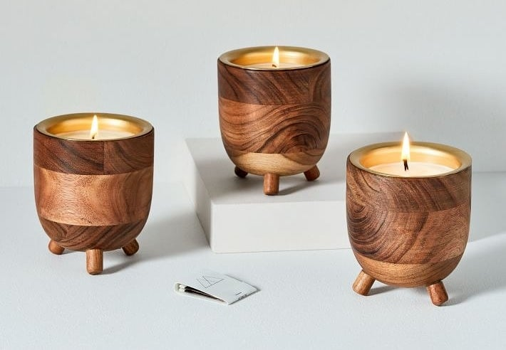 Three wooden barrel candles with legs on the bottom and a gold interior where the wax burns