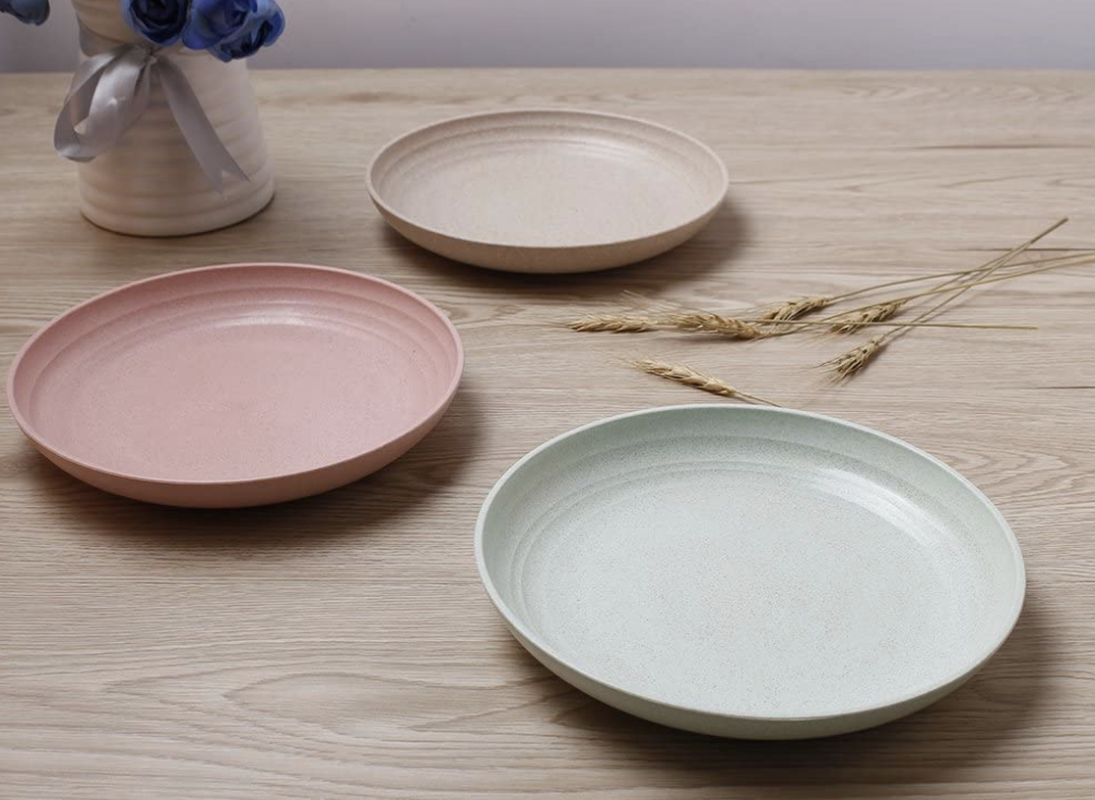 A set of three beige, pink, and pale blue dinner plates