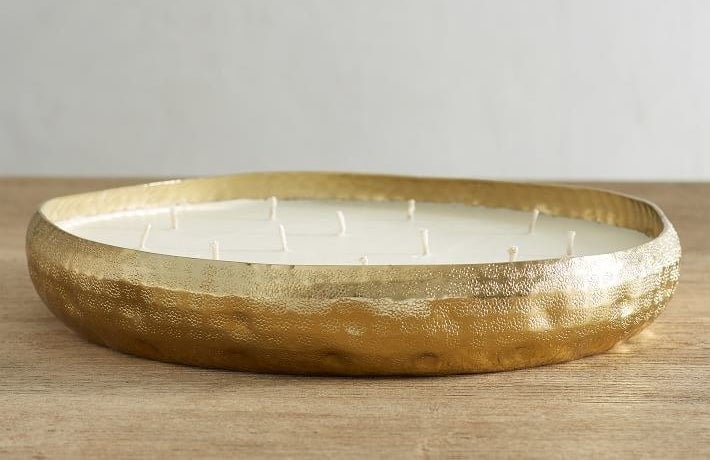 A large metal, gold candle with a hammered detailing and a multitude of wicks