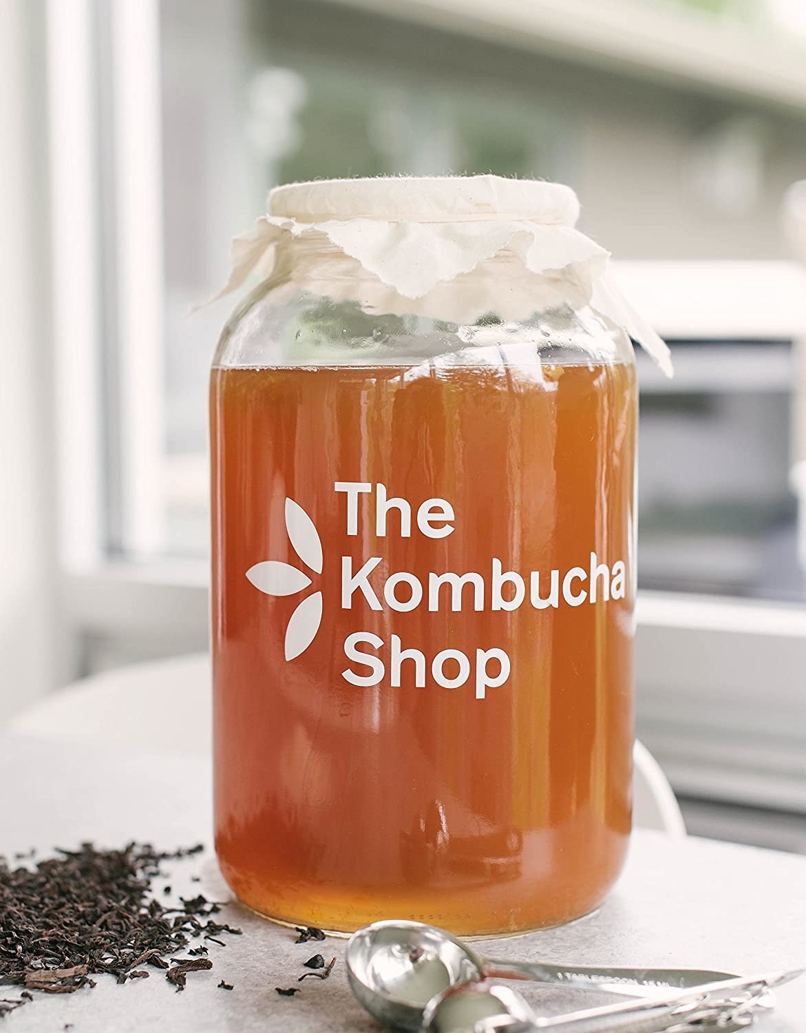A large jar of kombucha with a fabric lid