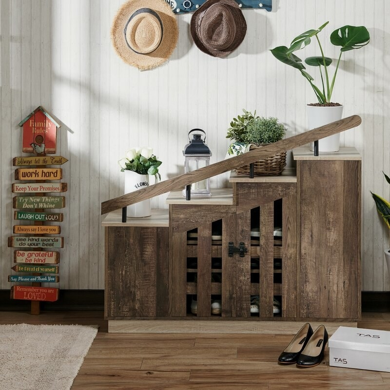 The cabinet in a reclaimed oak finish, featuring a stepped silhouette topped with a decorative railing