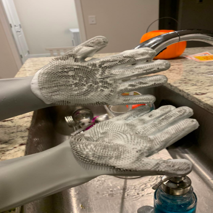 A reviewer wearing the gray gloves with the palms covered in suds
