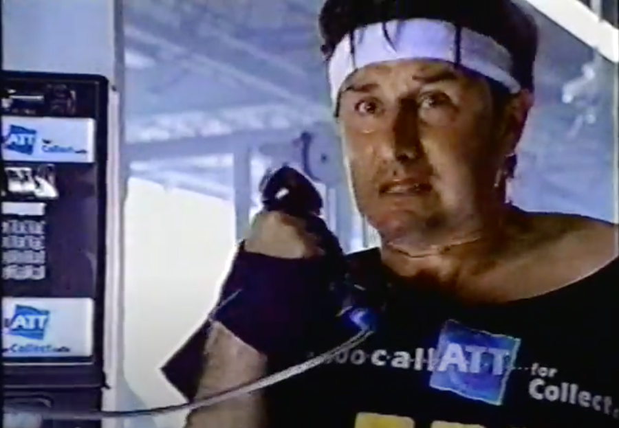 A screenshot of David Arquette in workout clothes picking up a payphone