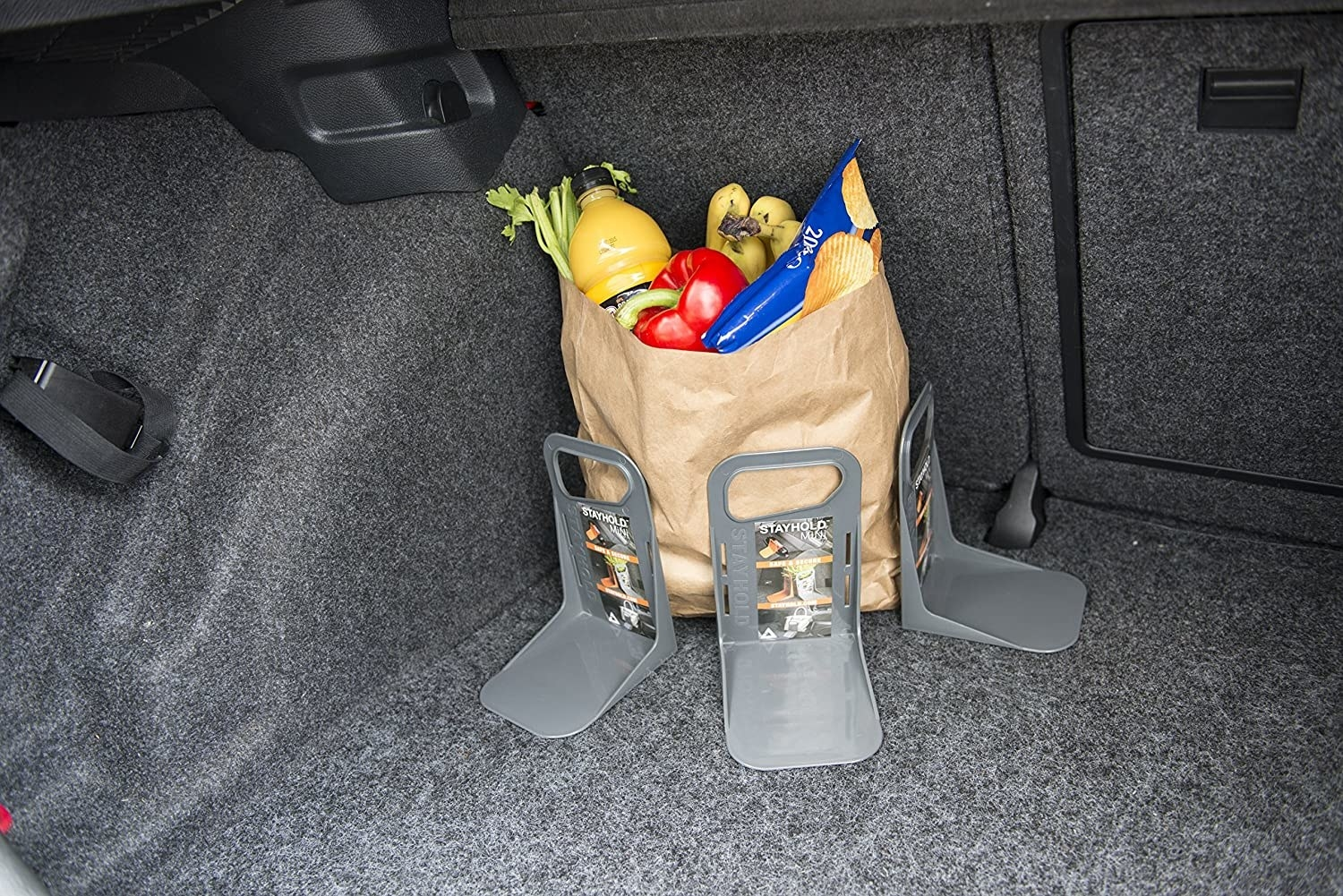 The L-shaped tools holding up a paper bag of groceries in a trunk
