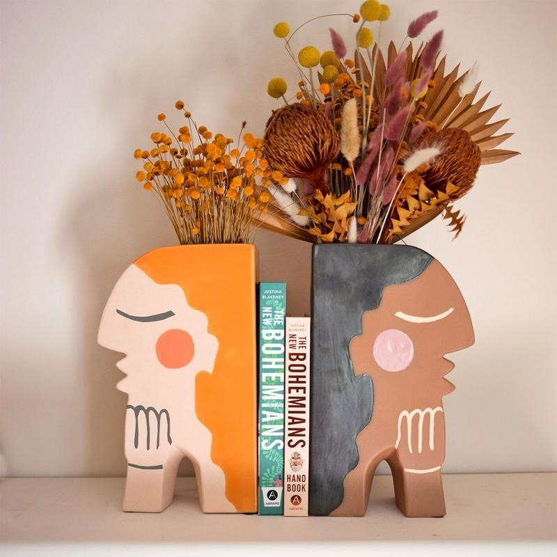 The two bookends in the shape of women's facial side profiles, one is of a white woman and the other of a Black woman