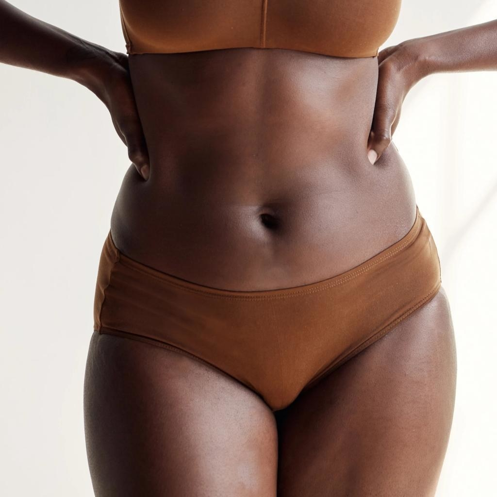 A model with dark skin in nude lingerie to match her skin tone