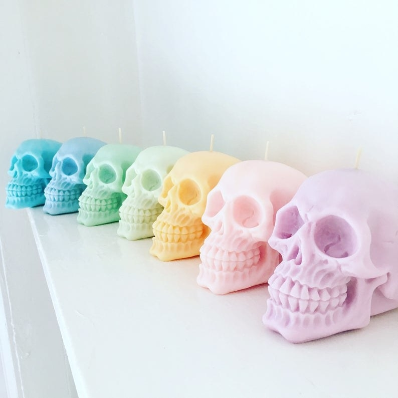 Seven candles in the shape of a skull all in different pastel colors