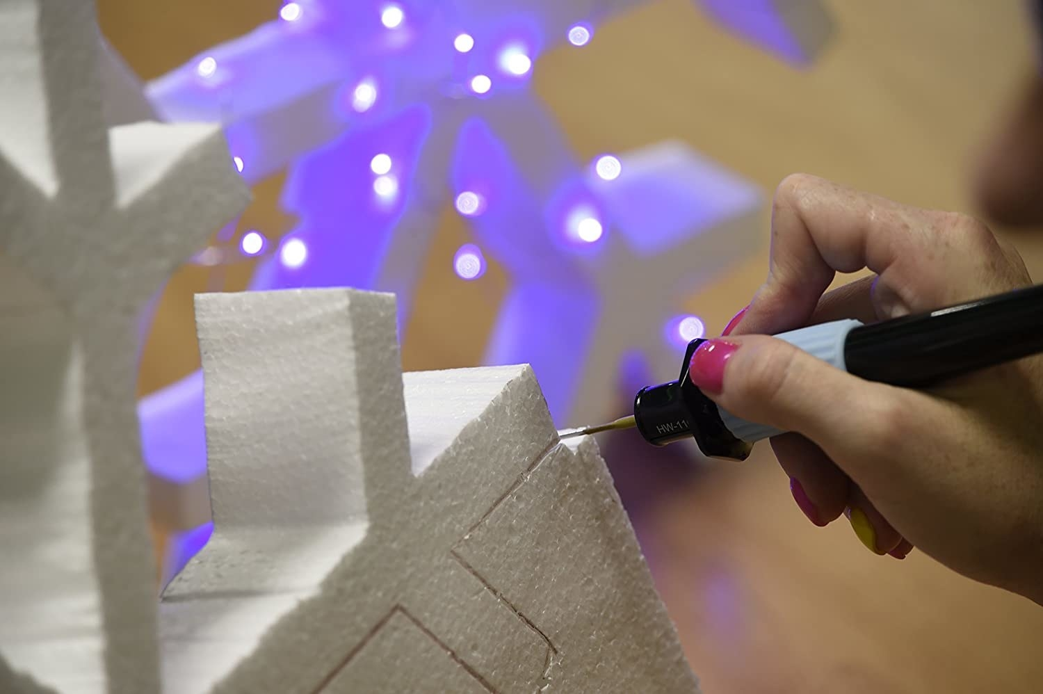 A person carving giant snowflakes out of foam with the heat tool