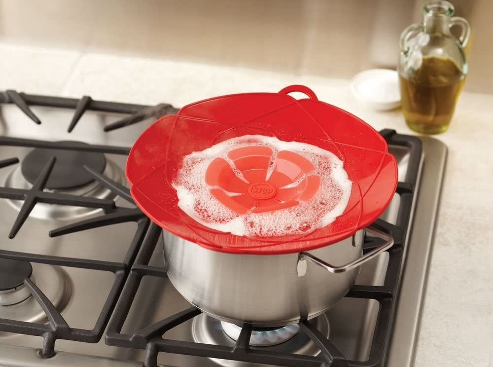 The spill stopper in red on top of a pot on a stove with water boiling inside, illustrating that it will not boil over