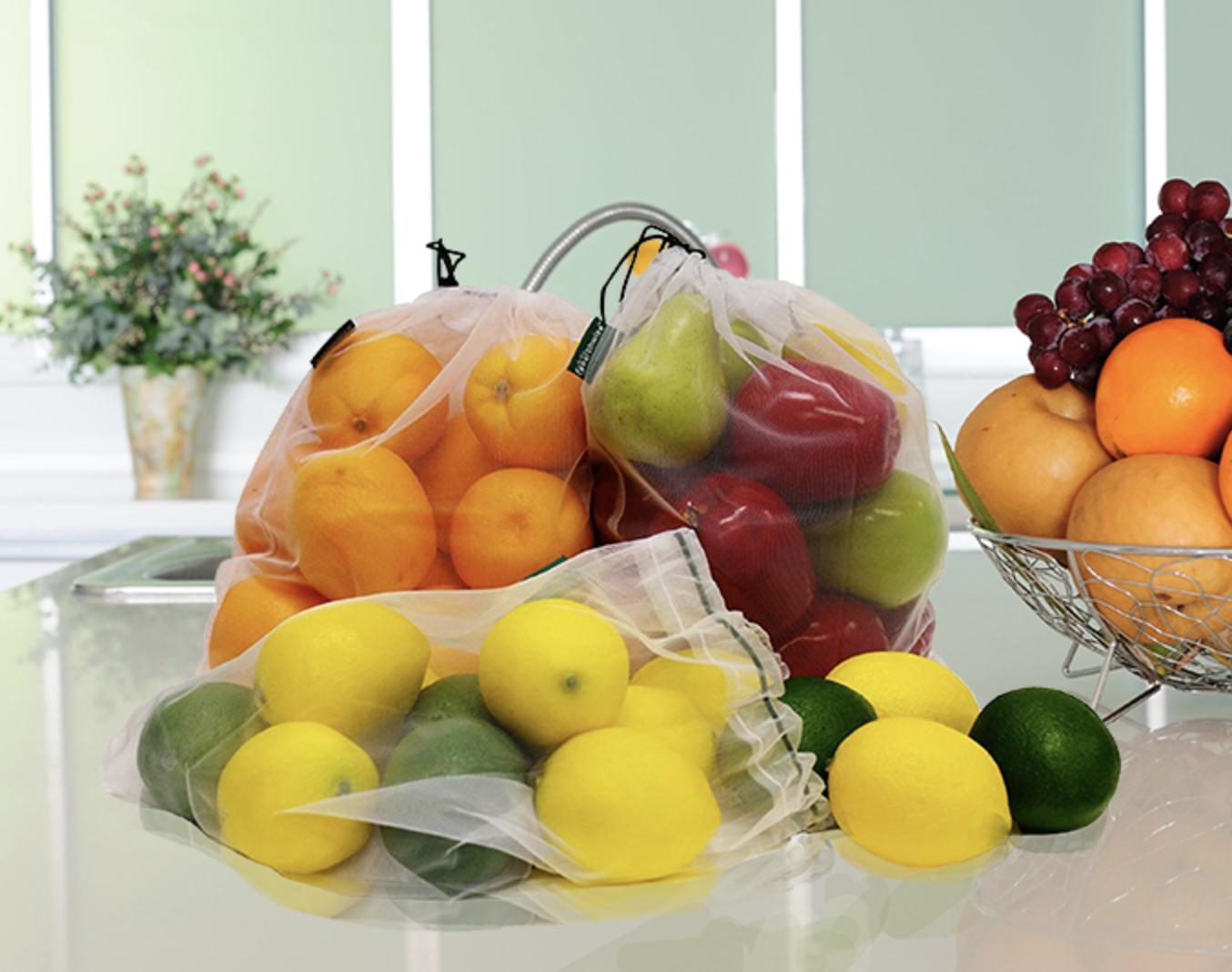 Three mesh bags full of fresh fruit