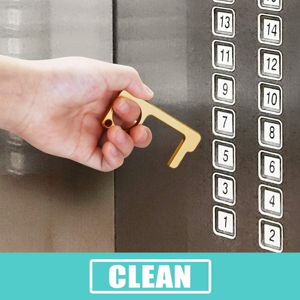 A hand using the tool to push an elevator button