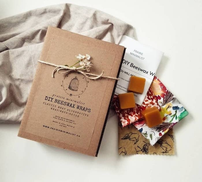 A product shot of printed packaging wrapped in twine with three fabric scraps and three cubes of wax