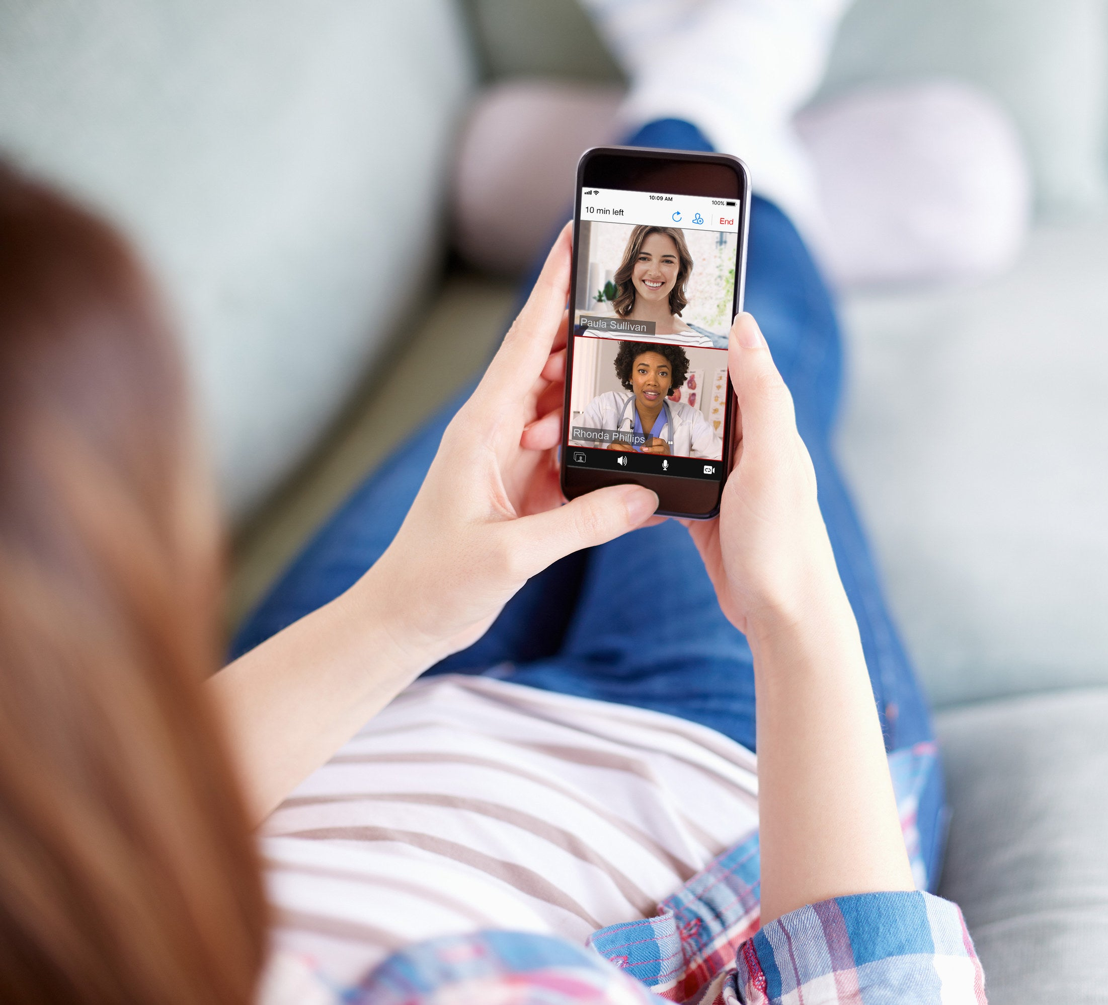 A woman lays on her couch and holds her phone in front of her, which displays her video conferencing with her therapist
