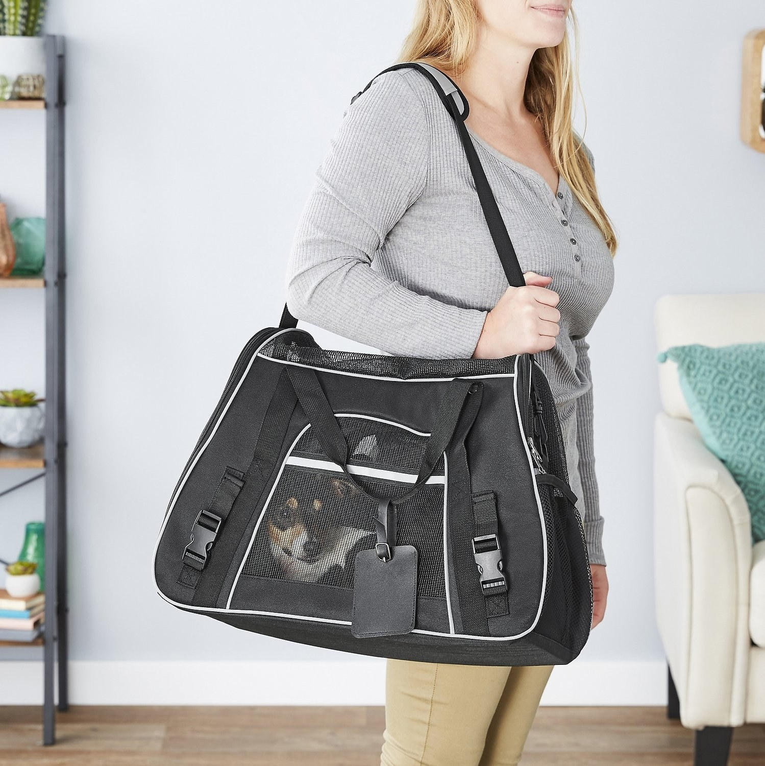 model holding the carrier, which looks like a mesh duffle bag, with a dog inside