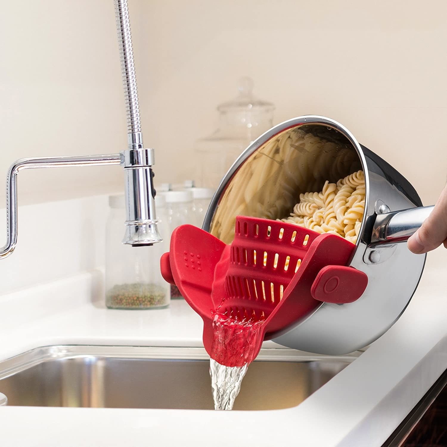 A person using the clip-on strainer to strain a pot of pasta in their sink