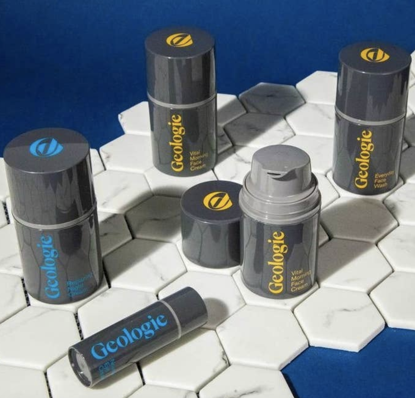Gray Geologie skincare product bottles arranged on a tile counter