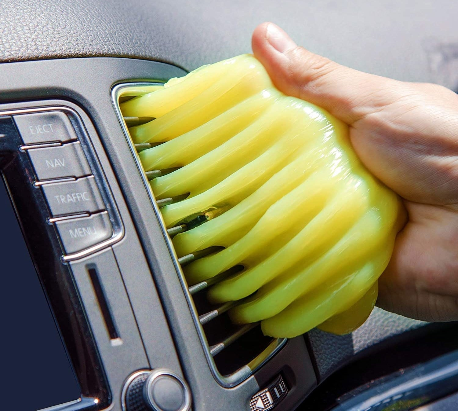A hand pulling the gel out of a car vent
