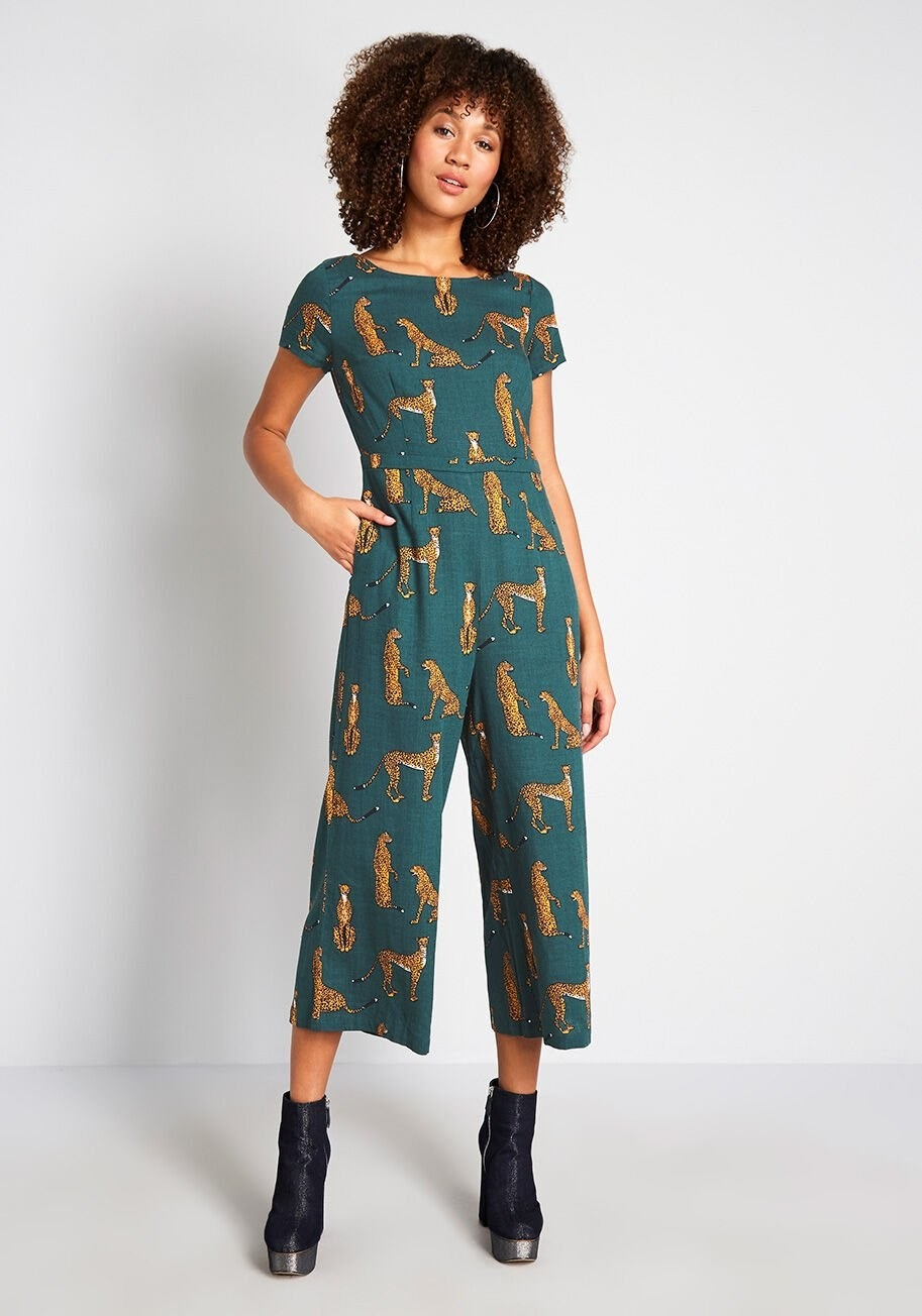 Model wearing the dark green jumpsuit featuring cheetah animals in different poses throughout the entire garment. Jumpsuit hits mid-shin, has short sleeves, and pockets.