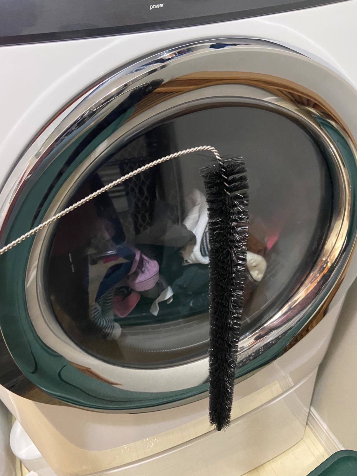 A reviewer holding the curved dryer brush