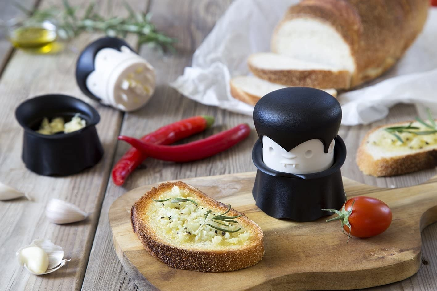 A handheld garlic chopper that looks like a vampire with a small face and long black robe