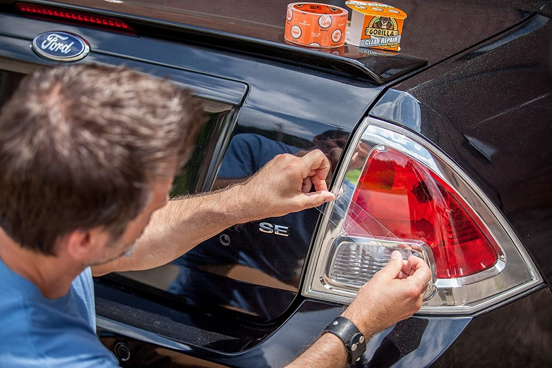 A person putting a piece of Gorilla tape onto their broken car light