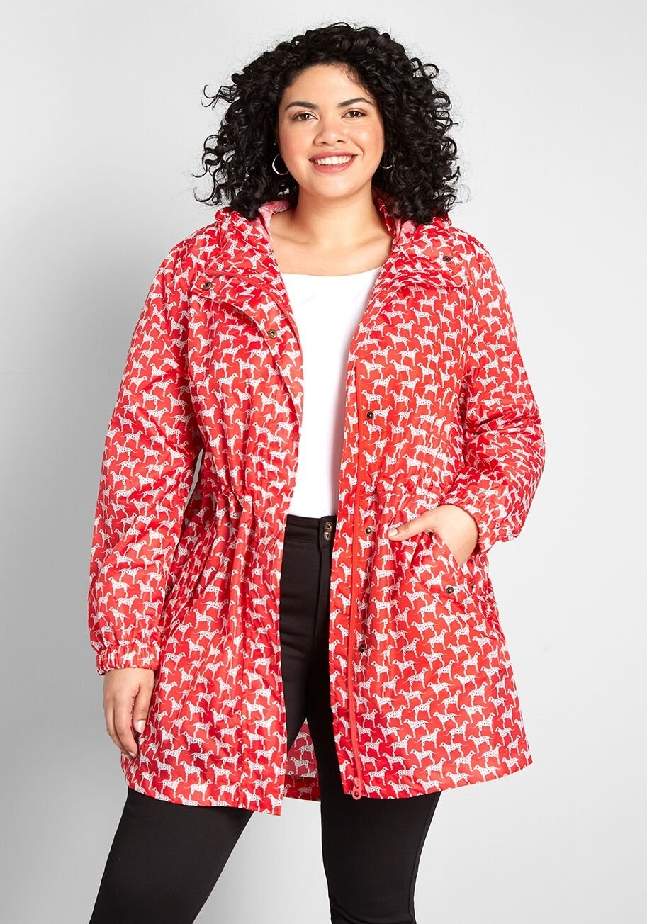 Model wearing red raincoat with little dogs printed all over