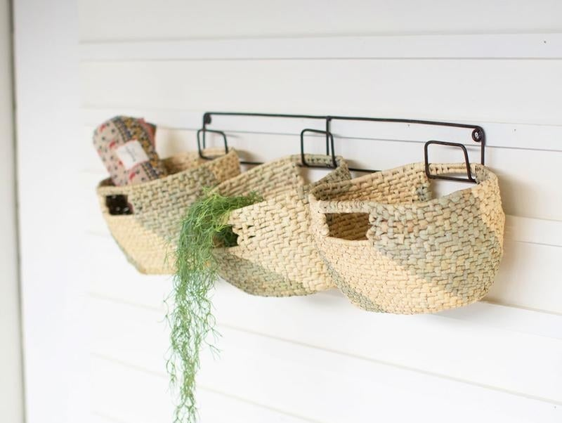 Three woven baskets with a tan and green diagonal design attached to a wall hook with three prongs on a wall