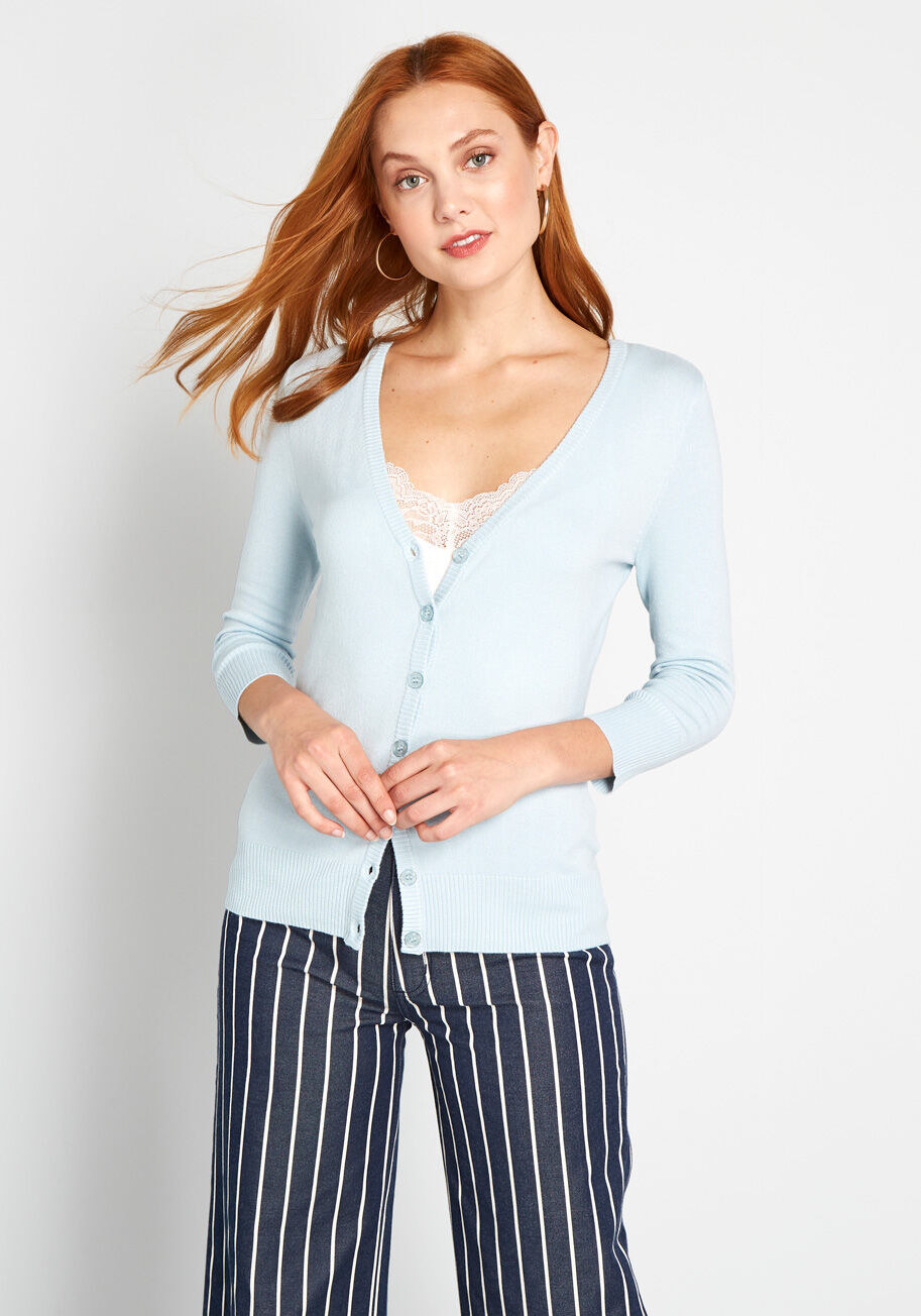 Model wearing light blue cardigan buttoned up with a lace tank underneath that peeks out