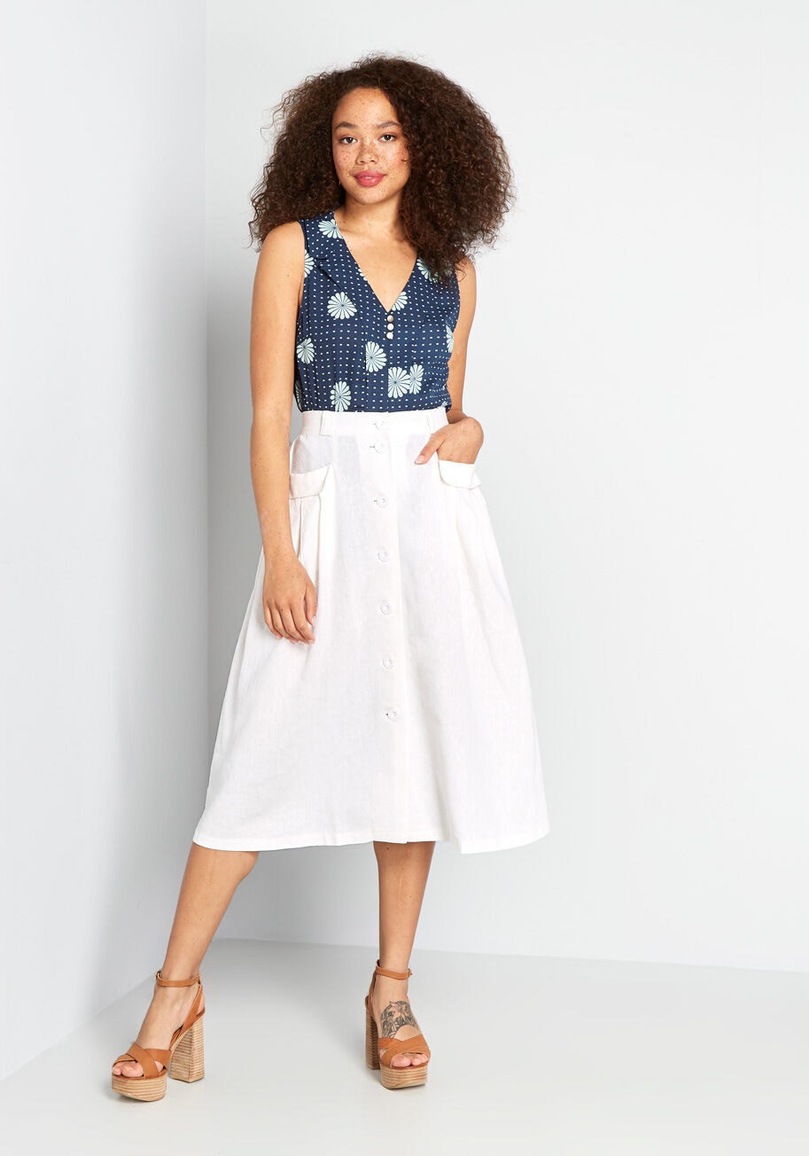 Model wearing skirt that falls right past the knees and has buttons all the way down the front