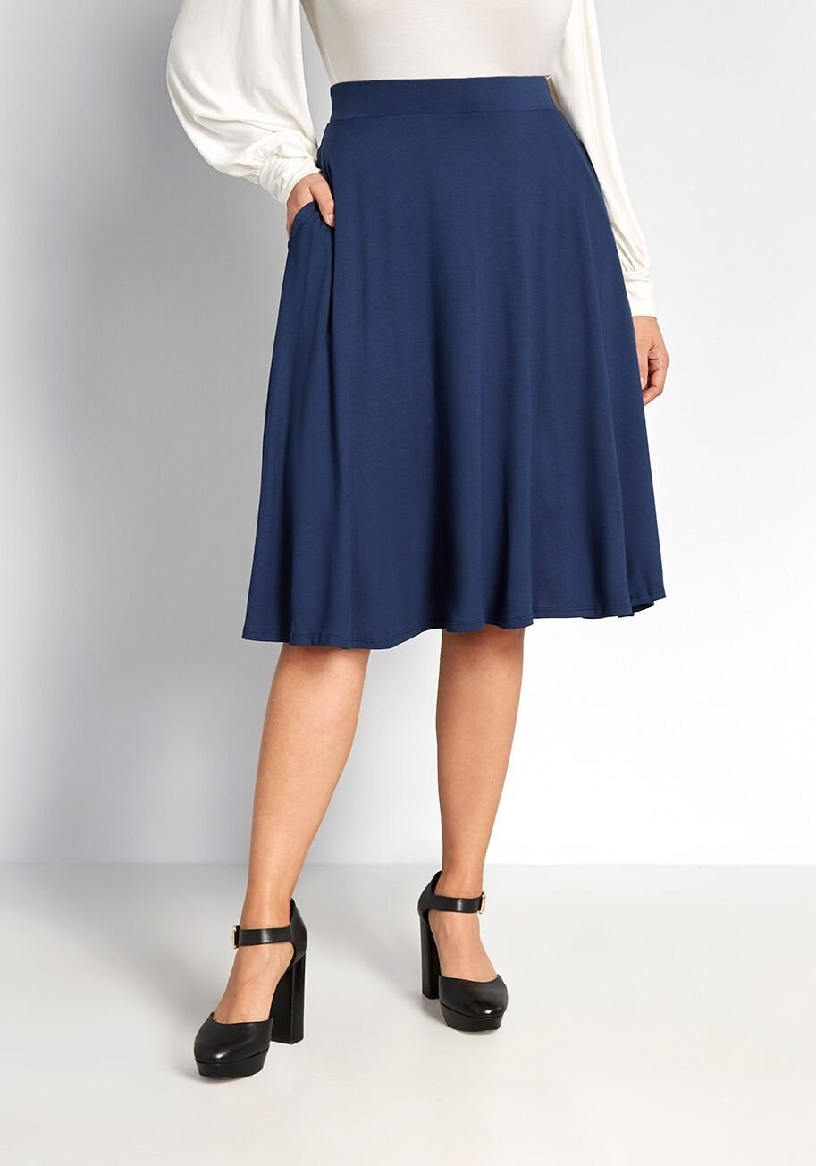 Model with hand in pocket wearing navy blue A-line skirt that hits right at the knees