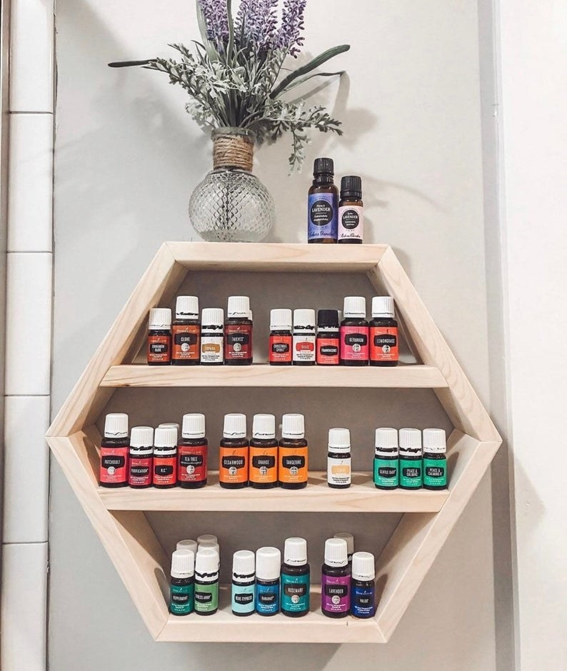 Hexagon-shaped wall shelf with three shelves filled with a rainbow variety of essential oil bottles