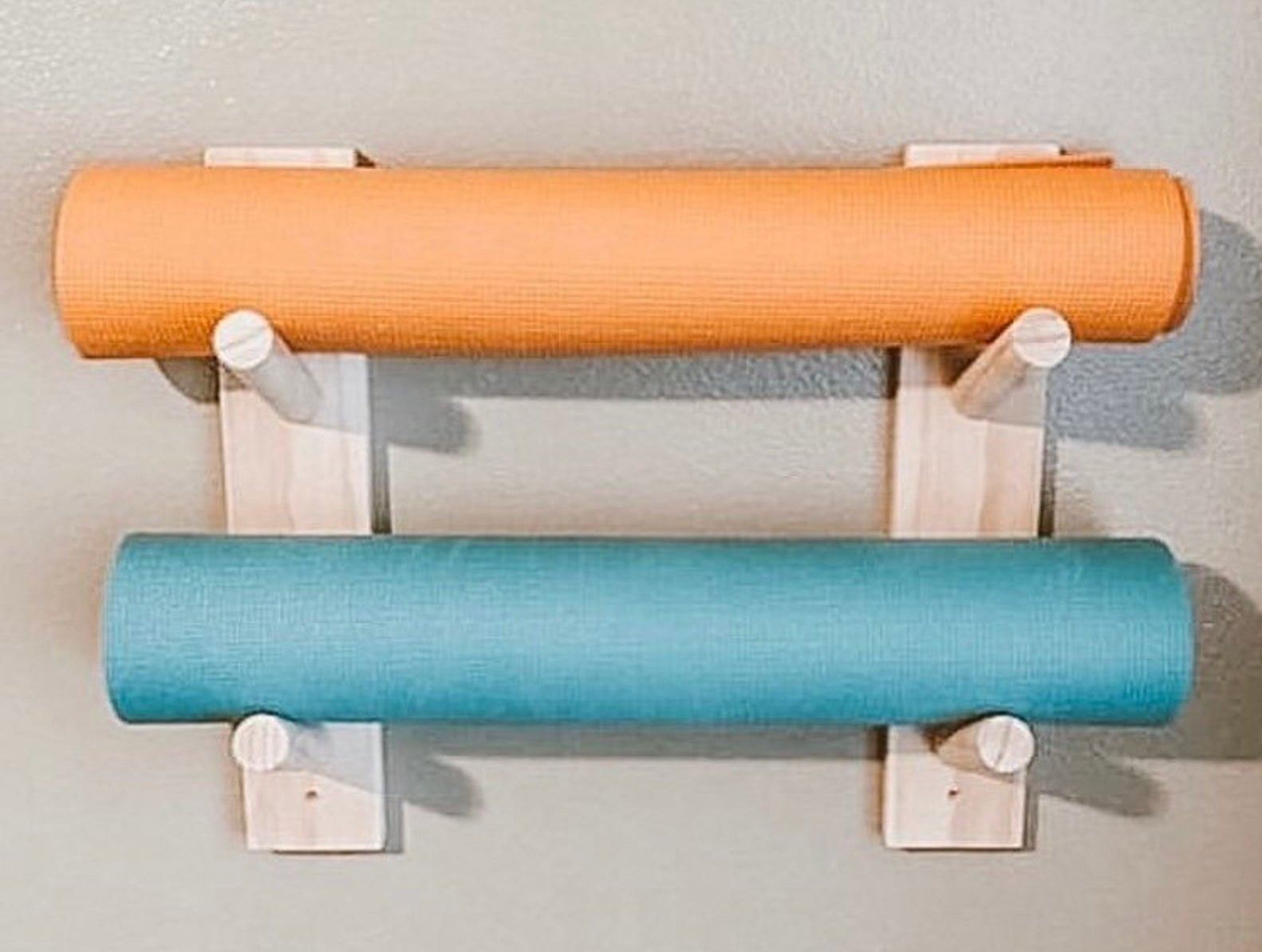 Wood rack with four pegs attached to a wall with two yoga mats between two of the pegs