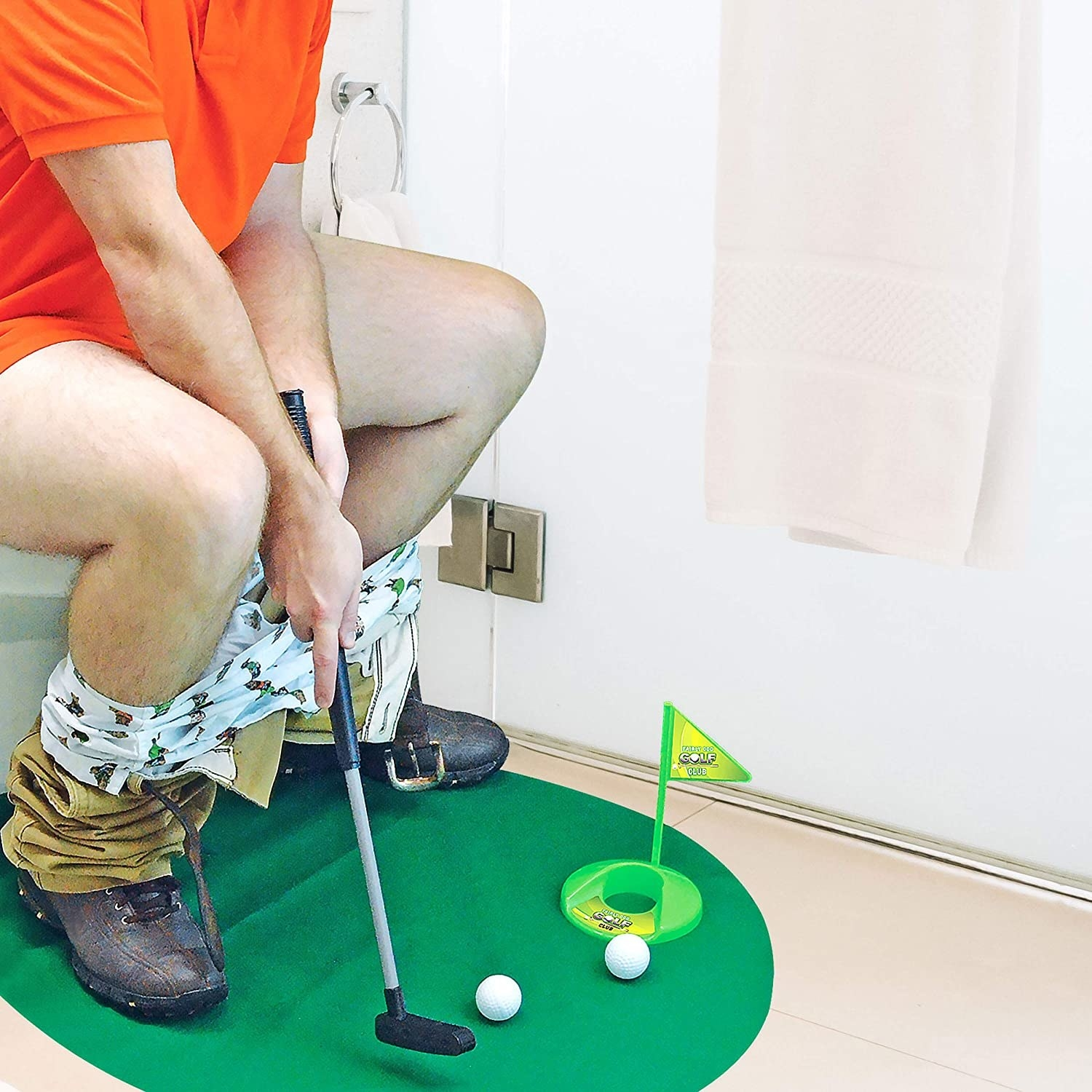 A person plays golf while sitting on the toilet