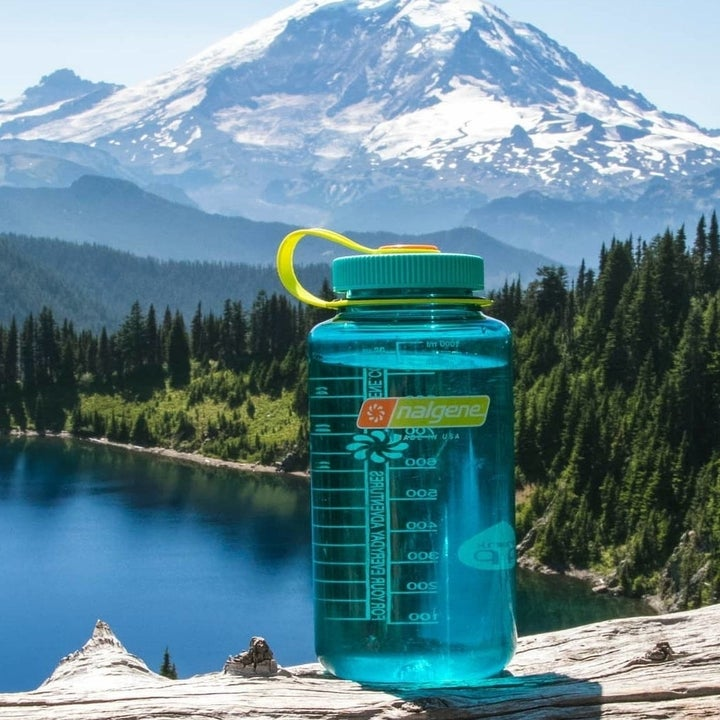 teal nalgene in front of a lake and mountains