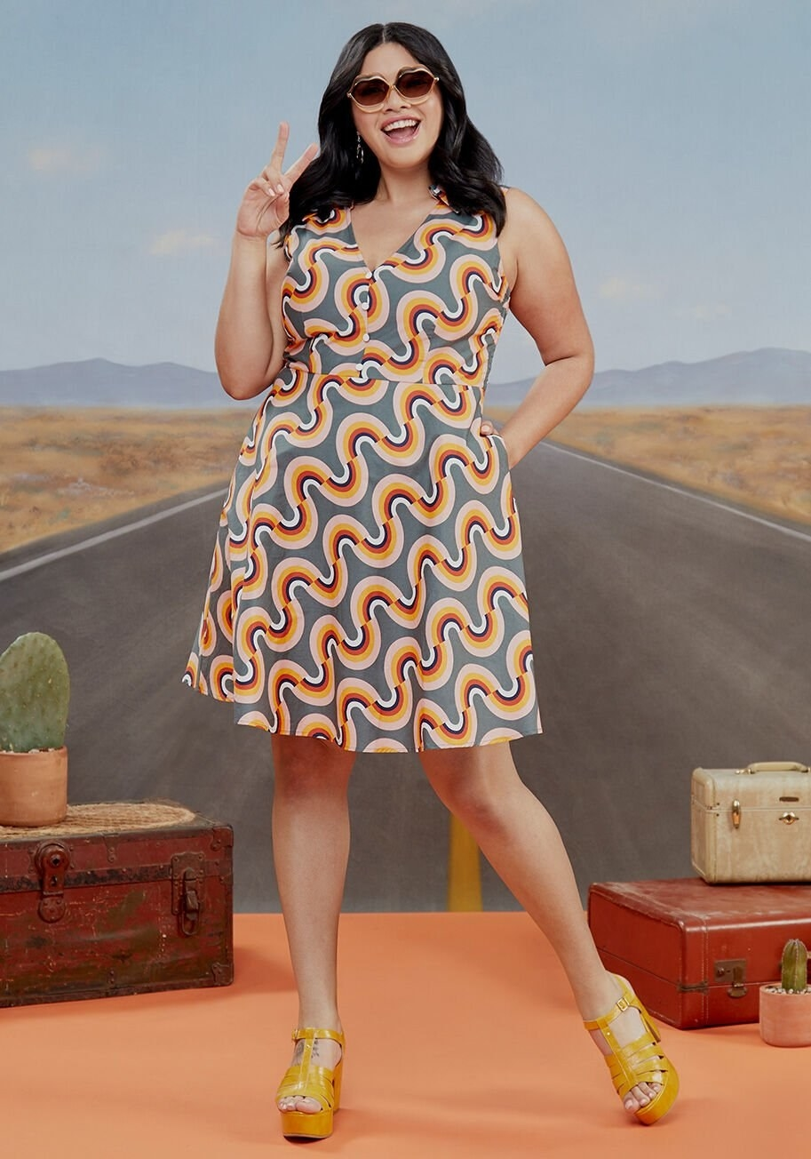 Model wearing dress with hand in pocket that hits right above the knee