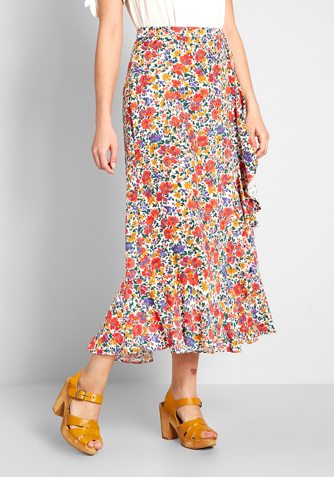 Closeup of a model wearing the skirt in a bright red, purple, and yellow flowers floral pattern that comes down to the ankles