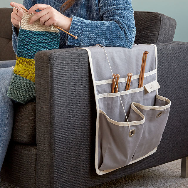 The knitting caddy over a couch arm with knitting needles and carn in the pockets with a model knitting next to it