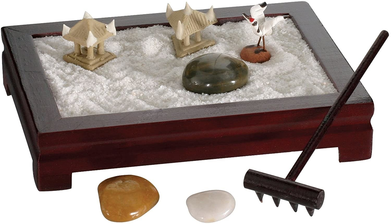 a sand garden with crystals and a raking tool