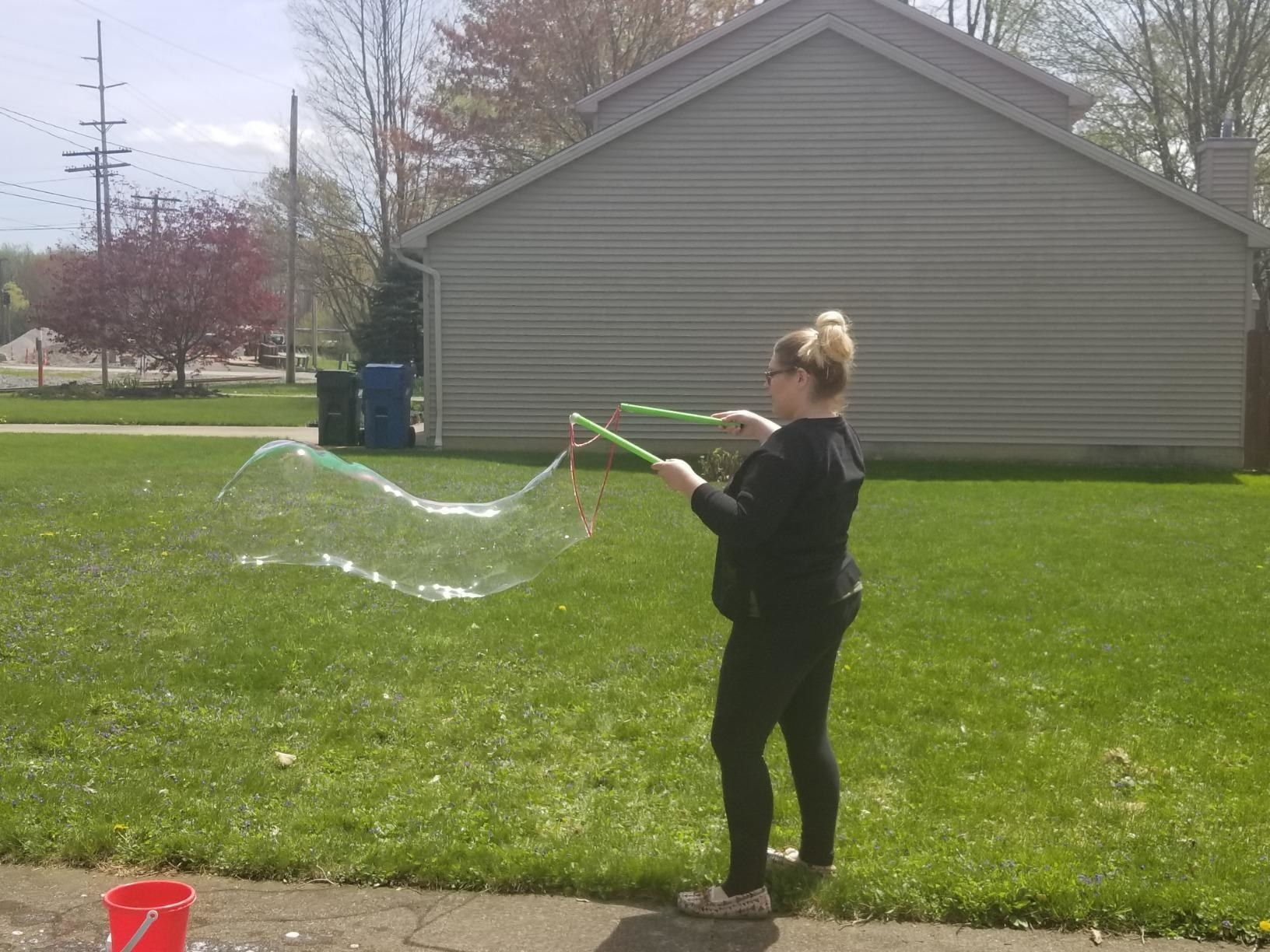 A reviewer using the kit to make a giant, long bubble