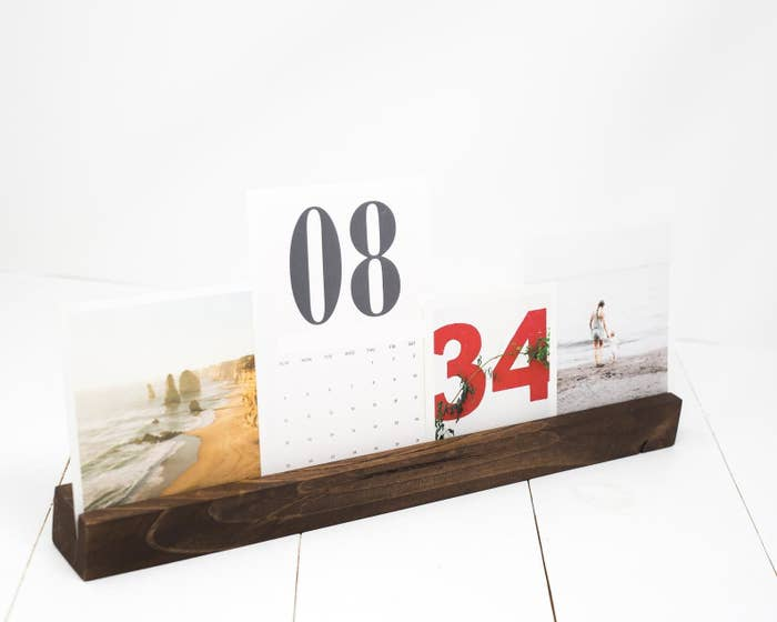 A thin rectangular wooden holder with slit down the middle with assorted pictures and a calendar in it
