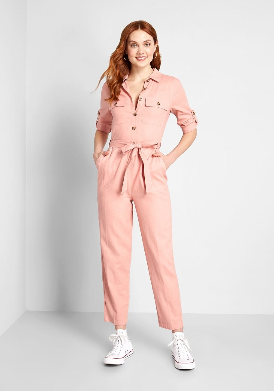 Model wearing a pink utility ankle-length jumpsuit with hand in pocket