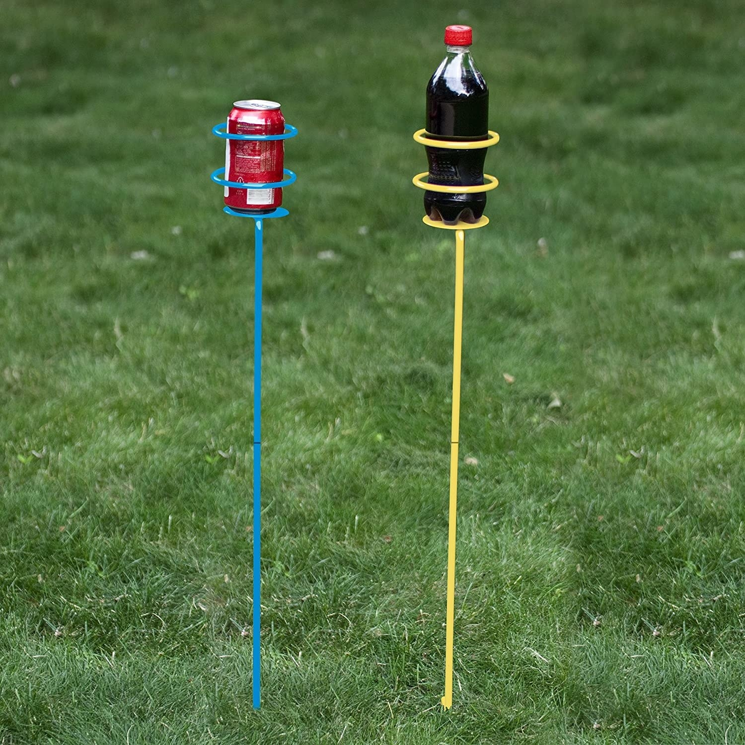 The drink stakes sticking out of grass and holding a can and bottle of soda