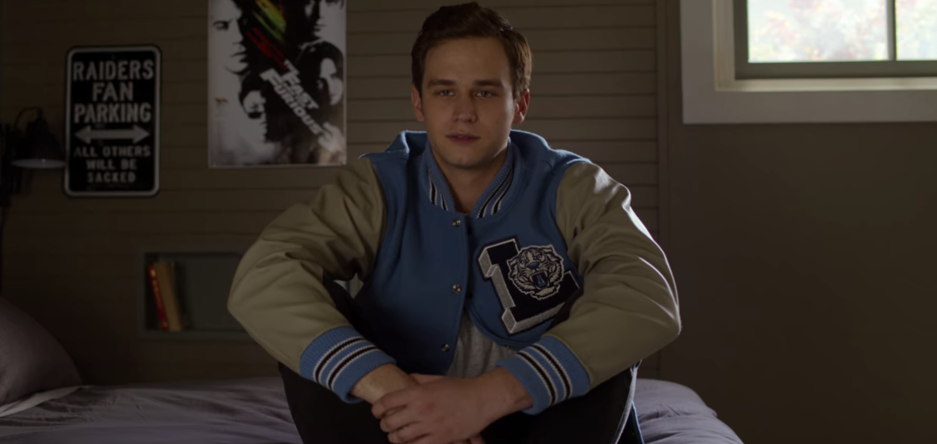 "Brandon Flynn as Justin in ""13 Reasons Why"" sitting on Clay's bed in his letterman jacket"