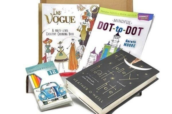 Coloring books, a hardcover book, and colored pencils