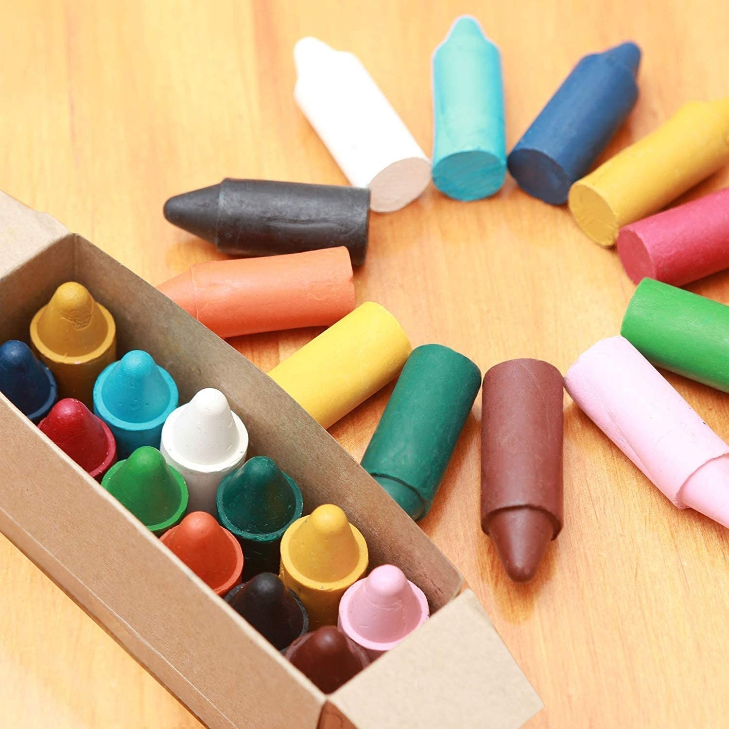 An open box of large, multi-colored crayons with some spread in a circle on a table
